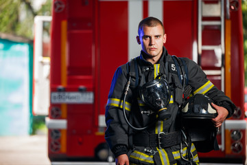 Photo of fireman with gas mask and helmet near fire engine