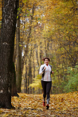 Image of sports brunette on morning run in autumn
