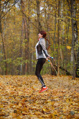 Full-length picture of young brunette jumping with rope at autumn forest