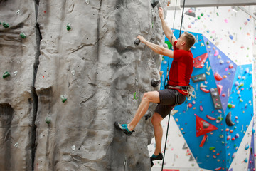 Photo from side of sports man in red T-shirt training on climbing wall