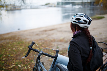 Photo from back of girl in helmet next to bicycle on pond