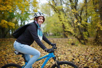 Picture of happy girl in helmet riding bicycle in autumn