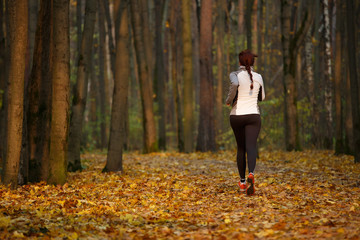 Image from back of young sports girl in running through forest