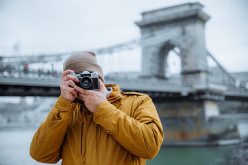 young man in hate taking picture on old retro camera. old chain bridge on background