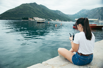 young adult woman sitting on pier with beautiful view of sea nd mountains. drone controller