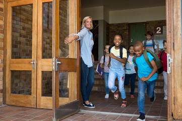 Group of elementary children running outside school