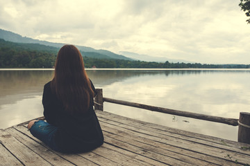 Closeup image of an asian woman sitting alone on an old wooden pier by the river with sky and mountain background