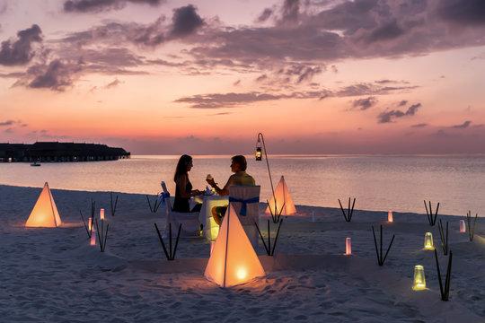 Romantisches Paar sitzt bei einem privatem Abendessen am tropischen Strand und genießt den Sonnenuntergang