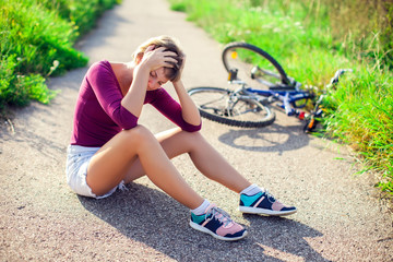 Woman with head injury after biking on bicycle. Sport, healthcare and people concept