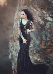 Brunette woman with tattoos posing with a snake. A girl in a black long dress in the desert with a Python.