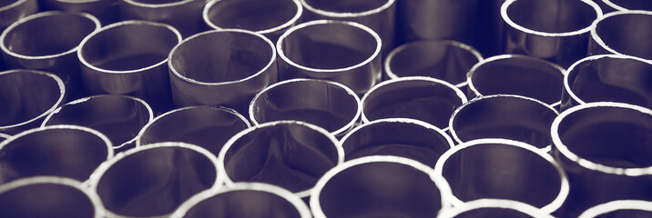 Round edges of metal pipes in the form of a background. Sections of pipes of different lengths. Banner