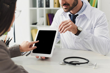 cropped image of doctor showing patient tablet with blank screen in clinic