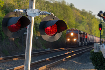 Close up of an active railroad crossing light with blurred on-coming train in background. Fotomurales
