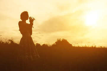 Young woman in dress with bouquet of flowers in hands at sunset in the field. Tinted warm silhouette image