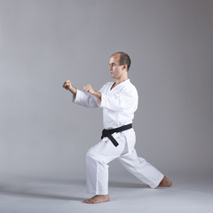 An athlete with a black belt and in karategi performs a formal karate exercise