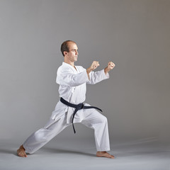 On a gray background, an athlete with a black belt trains a formal karate exercise