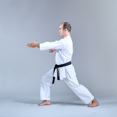 Sportsman with a black belt and karategi trains formal karate exercises Kaderov