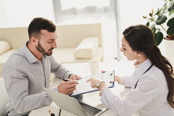 man signing insurance claim form while doctor pointing at it in office with laptop