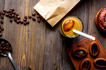 coffee with ice in glass on wooden background top view