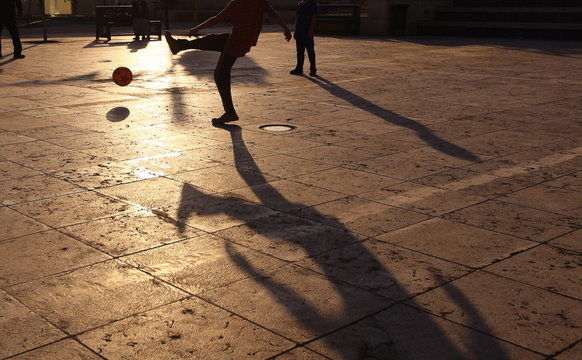 Shadows of people playing in football in a street of the city at the sunset