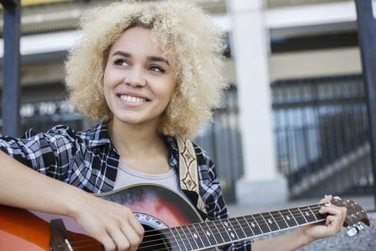 Happy African-American girl playing the guitar the street