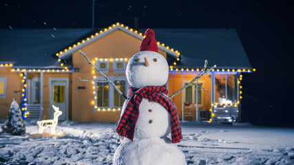 Funny Snowman Wearing Hat and Scarf Standing in the Backyard of the Idyllic House Decorated with Garlands on Christmas Eve. Soft Snow is Falling on that Magical Winter Evening.
