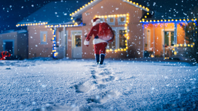 Low Angle Shot of Santa Claus with Red Bag, Walks into Front Yard of the Idyllic House Decorated with Lights and Garlands. Santa Bringing Gifts and Presents at Night.