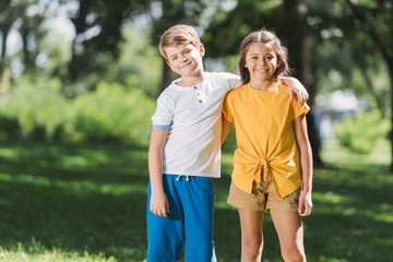 beautiful happy children embracing and smiling at camera in park