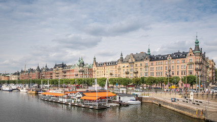 Boat and street cafe in old part of Stockholm, view from the river, 2 august 2018 Sweden