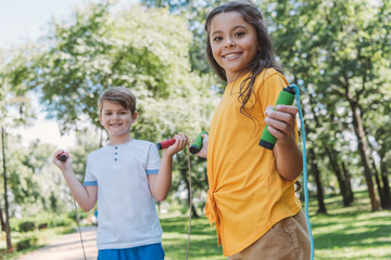 adorable happy kids hiking skipping ropes and smiling at camera in park