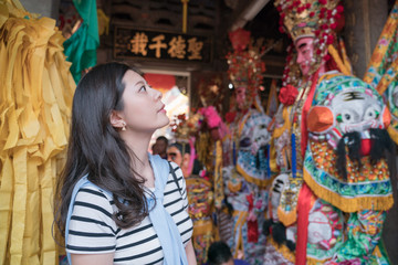 asian woman sightseeing in the temple. by the background of god and religious sculptures