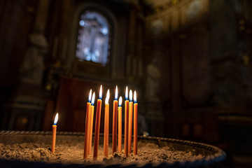 Many burning candles with shallow depth of field in a sandstone candlestick in a church with a crucifix in the background