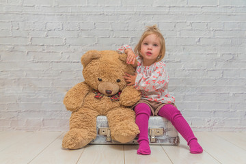 the girl, child with bear and suitcase on white brick wall background