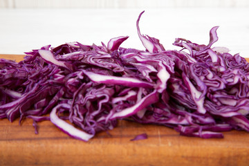 Chopped red cabbage on cutting board, close-up. Side view.