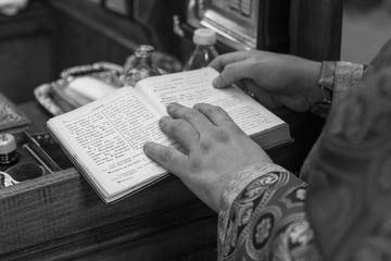 an Orthodox priest reads from the Bible during a Christian ritual in a small church. Light grain effect and natural light in black and white.