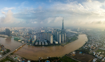 Wall Mural - Aerial view of Ho Chi Minh City skyline and skyscrapers in center of heart business at Ho Chi Minh City downtown. Panorama of cityscape on Saigon river in Ho Chi Minh City at Vietnam at sunrise scene
