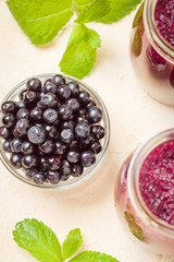 Blueberry smoothie decorated with fresh green mint leaves and raw ripe berries on yellow pastel background
