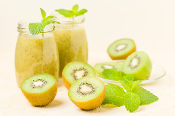 Kiwi smoothie decorated with fresh green mint leaves and raw ripe cut fruit on yellow pastel background.