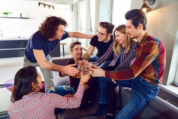 Group of young people with a mug of beer at a meeting of friends.