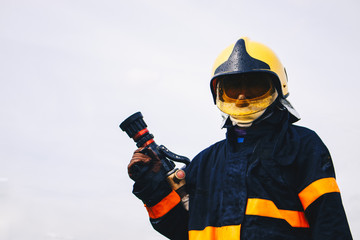 firefighter holding fire hoses in uniform and an oxygen mask