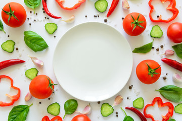 Colorful salad ingredients pattern made of tomatoes, pepper, chili, garlic, cucumber slices, basil and empty plate on white background. Cooking concept. Top view. Flat lay. Copy space Wall mural