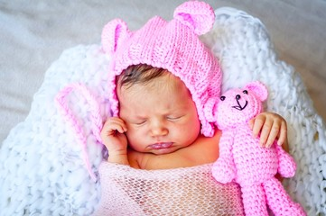Sweet Caucasian newborn baby girl in a cute pink hat with ears hugging a teddy bear. Newborn photo session studio stock image.
