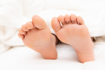 feet of a boy lying on bed