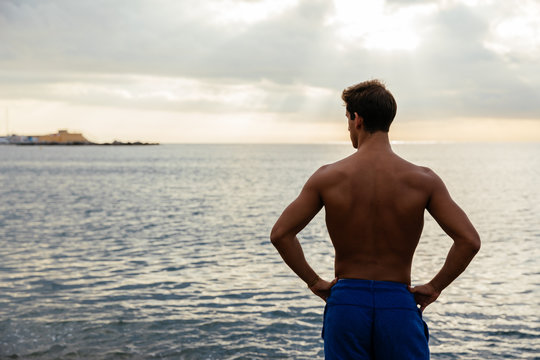 Young athlete posing by the sea.