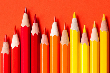 Color pencils isolated on red background.