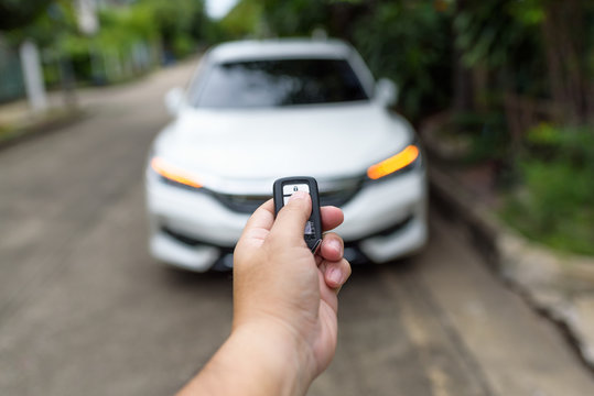 A man's hand is pressing the remote to lock or unlock the car door.