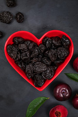 Dried Plums Pitted Prunes in Heart Shaped Bowl. Selective focus.