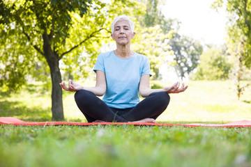 Senior woman in lotus pose sitting on green grass