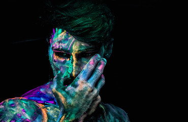 Headshot of young man painted in fluorescent paint on face and muscular torso, in studio shot with UV light