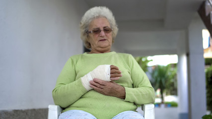 Old woman massage her injured broken hand sitting, cinematic dof